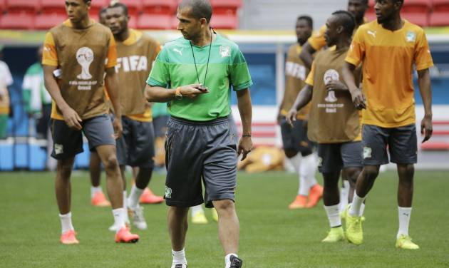 Ivory Coast coach Sabri Lamouchi, center, walks on the pitch a training session at the Estadio Nacional in Brasilia, Brazil, Wednesday, June 18, 2014. Ivory Coast plays in group C of the 2014 Brazil soccer World Cup. (AP Photo/Sergei Grits)