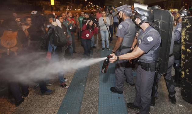 A police officer pepper sprays strikers and protesters during a clash with riot police in front of the Ana Rosa metro station, in an ongoing subway strike by operators, in Sao Paulo, Brazil, Monday, June 9, 2014. Authorities are deeply worried about the strike because the subway is the main means of transportation for World Cup fans scheduled to attend Thursday's opening match when Brazil takes on Croatia. The stadium is about 20 kilometers (12 miles) east of central Sao Paulo, where most tourists stay. (AP Photo/Mario Angelo)