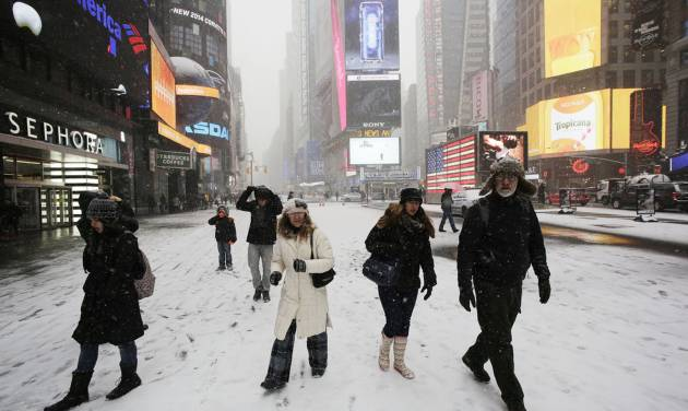 Pedestrians make their way through a snowfall, Tuesday, Jan. 21, 2014 in New York's Times Square. A storm is sweeping across the Mid-Atlantic and New England. The National Weather Service said the storm could bring 8 to 12 inches of snow to Philadelphia and New York City, and more than a foot in Boston. Bitterly cold air with wind chills as low as 10 degrees below zero was forecast. (AP Photo/Mark Lennihan)