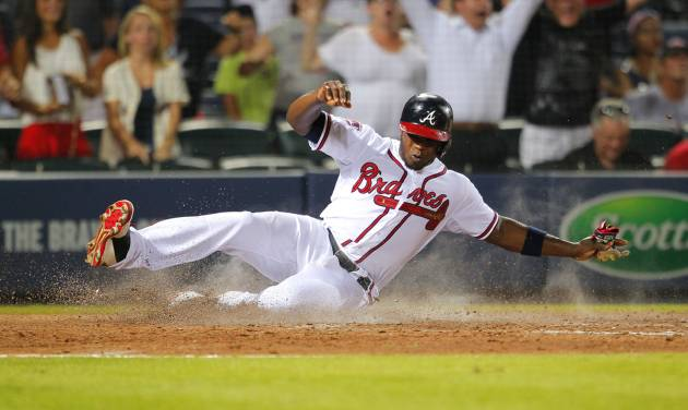 Atlanta Braves Justin Upton (8) slides in to score in the ninth inning of a baseball game against the Philadelphia Phillies Monday, June 16, 2014, in Atlanta. (AP Photo/Todd Kirkland)