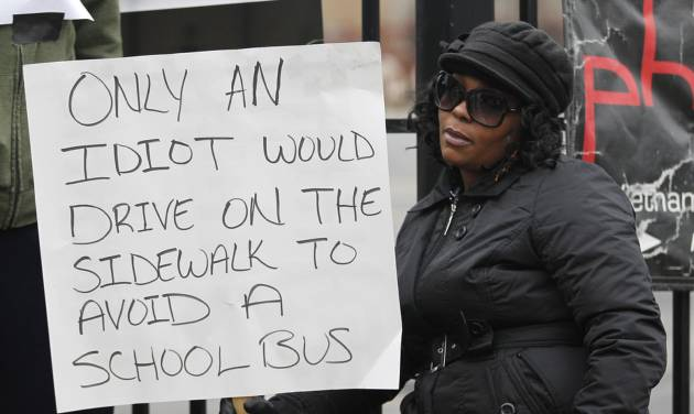 Shena Hardin holds up a sign to serve a highly public sentence, Wednesday, Nov. 14, 2012, in Cleveland for driving on a sidewalk to avoid a Cleveland school bus that was unloading children. Cleveland municipal judge Pinkey S. Carr ordered 32-year-old Hardin to serve the highly public sentence for one hour Tuesday and Wednesday. (AP Photo/Tony Dejak)