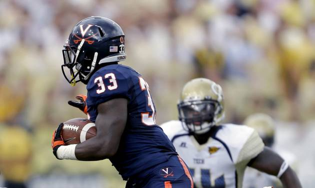 """FILE - In this Sept. 15, 2012, file photo, Virginia running back Perry Jones (33) jumps over teammate Oday Aboushi (72) and Georgia Tech linebacker Jeremiah Attaochu, bottom, during the first quarter of an NCAA college football game in Atlanta. Virginia's players say the signs of improvement are all there. The offensive line has come together and Perry Jones, the player they call """"Superman,"""" has actually been seen running into gaping holes the past few weeks. Jones and the Cavaliers hope it shows when they host Maryland on Saturday. (AP Photo/David Goldman, File)"""