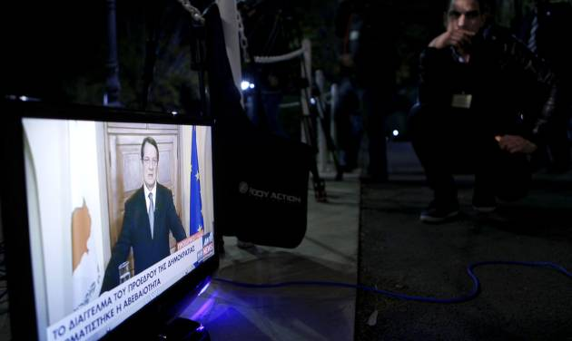 A TV channel employee watch the Cyprus' President Nicos Anastasiades speaks during a live, televised address to the nation from the Presidential Palace in the capital Nicosia, Cyprus, Monday, March 25, 2013. A deal to provide Cyprus with an international bailout was clinched in the early hours of Monday in a Brussels meeting between the 17-nation eurozone's finance ministers. (AP Photo/Petros Karadjias,Pool)