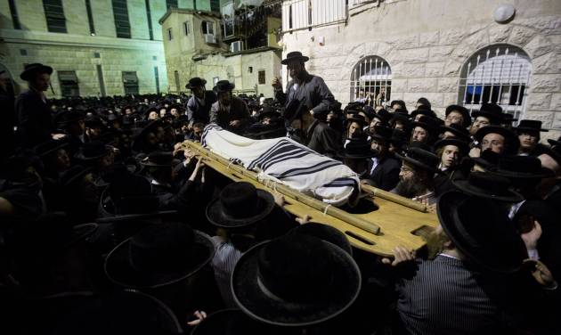 "An ultra-Orthodox Jewish man carries the body of Avrohom Wallis during his funeral in Jerusalem, Monday, Aug. 4, 2014. An assault carried out with a construction vehicle served as another reminder of the tense climate. Israeli TV stations broadcast a series of amateur videos of the attack, in which a Palestinian man used the front shovel of a construction excavator to ram a bus and tip it over. Police said a man who worked at the site was run over and killed by the construction vehicle. He was identified as a 29-year-old religious inspector whose job was to ensure that ancient graves were not damaged by construction work. A policeman who happened to be in the area shot the driver, who was identified as a resident of a Palestinian neighborhood in east Jerusalem. The man's uncle, Hisham Jaabis, said the incident was a traffic accident and that his nephew had been gunned down in cold blood while trying to dodge the bus. ""All of them started shooting at him,"" he said. In the past, Palestinian attackers have gone on deadly rampages with bulldozers in Jerusalem traffic. (AP Photo/Sebastian Scheiner)"