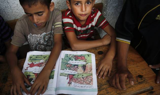 Palestinian boys read at a United Nations school where dozens of families have sought refuge after fleeing their homes following heavy Israeli forces' strikes in Beit Hanoun, northern Gaza Strip, Saturday, July 19, 2014. (AP Photo/Lefteris Pitarakis)