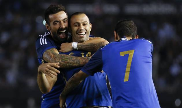 Argentina's Javier Mascherano, center, celebrates scoring against Trinidad and Tobago with teammates Ezequiel Lavezzi, left, and Angel Di Maria during an international friendly soccer match in Buenos Aires, Argentina, Wednesday, June 4, 2014. (AP Photo/Natacha Pisarenko)