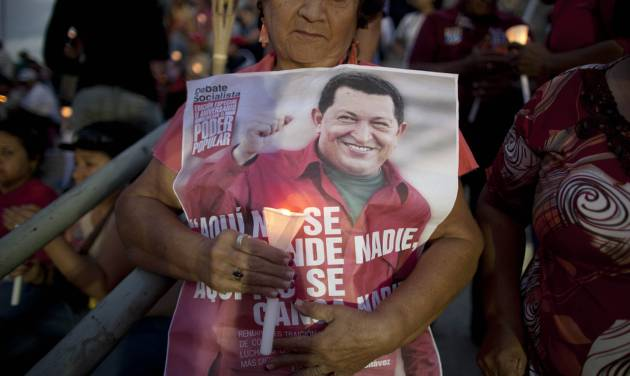 "A woman holds a candle along with a poster of Venezuela's President Hugo Chavez at a candlelight vigil to pray for his health as he remains in a hospital undergoing cancer treatment, in Caracas, Venezuela, Friday, Feb. 22, 2013. The Venezuelan government provided an update on Chavez's condition Thursday night, saying that he remained at a military hospital in Caracas and that ""the medical treatment for the fundamental illness continues without presenting significant adverse effects."" (AP Photo/Ariana Cubillos)"