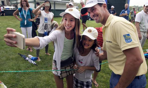 Canada's Mike Weir, of Canada, poses for a selfie with Kaylee Chin, left, and Maya Cunningham, center, during the pro-am event at the Canadian Open golf championship Wednesday, July 23, 2014 at Royal Montreal golf club in Montreal. (AP Photo/The Canadian Press, Ryan Remiorz)