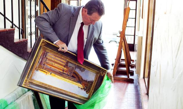 Judge Fred Howard of Provo's 4th District Court unwraps one of his paintings as he delivers a collection of his work to the Springville Museum of Art on Friday, Aug. 31, 2012 in Springville, Utah. The museum is exhibiting 33 of Howard's paintings, which all depict the organ in the LDS Church's Salt Lake City Tabernacle. (AP Photo/Daily Herald, Spenser Heaps)