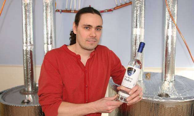 Rob Borland holds a prototype bottle of Long Winter Vodka as he poses in his distillery Sunday, March, 24, 2013. Borland and his wife Tara have launched Ursa Major Distilling, the first commercial distillery in the Fairbanks, Alaska, area. (AP Photo/Fairbanks Daily News-Miner, Jeff Richardson)