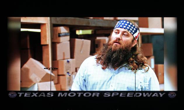 """Fans were able to watch tonight's episode of Duck Dynasty on Big Hoss, one of the stars, Willie Robertson on screen here, and his wife were in attendance at TMS. Texas Motor Speedway debuted their new Big Hoss TV screen, a 218 x 94 foot screen over the east grandstands of the racetrack, Wednesday, March 19, 2014. The first show to be seen on the screen by the public is Wednesday's episode of """"Duck Dynasty"""", sponsors of the upcoming April NASCAR race, the Duck Commander 500. (AP Photo/The Fort Worth Star-Telegram, Paul Moseley)"""