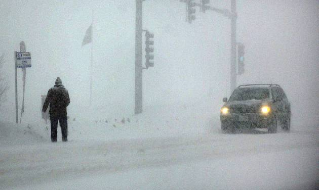 A man waits at a bus stop on Randall Road near Batavia, Ill., Monday, Feb. 17, 2014. The National Weather Service on Monday forecast up to 8 inches of snow for areas of northern Illinois and 5 inches in central Illinois. (AP Photo/Daily Herald, John Starks)