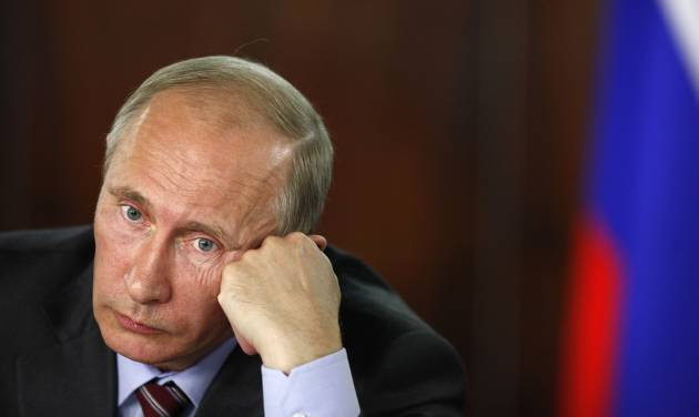 In this Friday, Aug. 19, 2011 file photo, Russian Prime Minister Vladimir Putin listens as he comes to discuss the problems of the disabled, organized by the People's Front in Moscow, with Russian national flag in the background. Vladimir Putin's return to the presidency on Monday May 7, 2012 will technically give him greater powers than he wielded as prime minister. The irony is that his position will be arguably weaker than at any time since he first came to power more than 12 years ago. (AP Photo/Alexander Zemlianichenko)