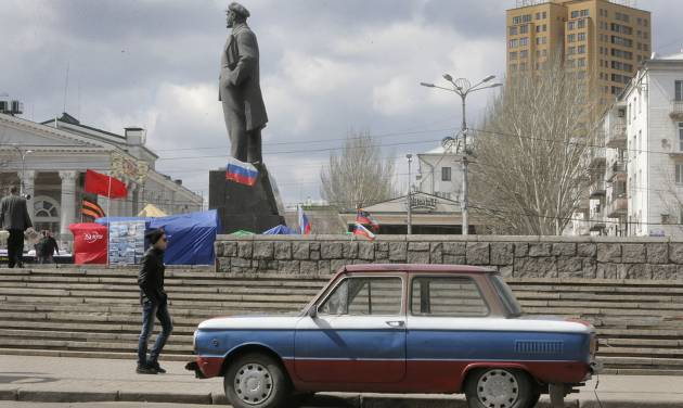A man passes by the car painted in the colors of Russian flag near a Soviet-era monument to Vladimir Lenin in the central square in Donetsk, Ukraine, Tuesday, April 15, 2014.  Several government buildings have fallen to mobs of pro-Moscow loyalists in recent days as unrest spreads across the east of the country. (AP Photo/Efrem Lukatsky)
