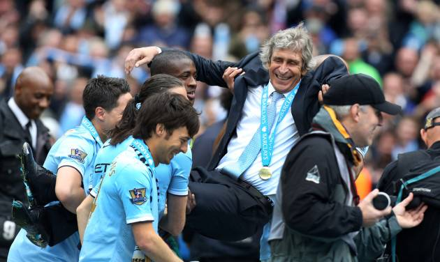 Manchester City's manager Manuel Pellegrini is carried by his players after the English Premier League soccer match between Manchester City and West Ham at the Etihad Stadium in Manchester, England, Sunday May 11, 2014.  Manchester City won the Premier League for the second time in three seasons on Sunday, completing its campaign with a comfortable 2-0 victory over West Ham that lacked any of the drama of its previous title.  (AP Photo/Jon Super)