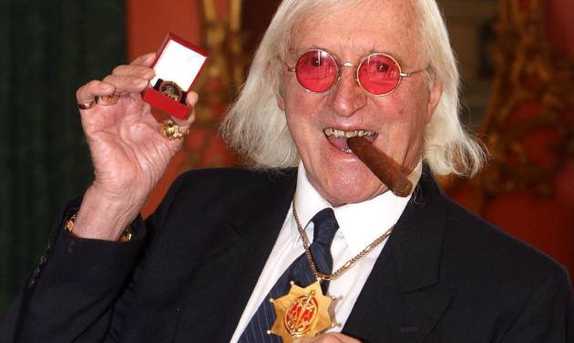 "FILE - This March 25, 2008 file photo shows Jimmy Savile holding a medal in London. At Savile's funeral in 2011, the priest delivering the homily was emphatic: the DJ and television host ""can face eternal life with confidence."" But a year on, Savile's reputation is in ruins. Police have branded him one of Britain's worst sex offenders, accused of assaulting underage girls over half a century. Like those who feted and praised him on that November day, millions are wondering: How could he have duped so many for so long? (AP Photo/Lewis Whyld/PA Wire)"