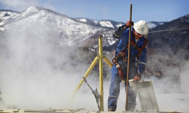 In this March 29, 2013 photo, a worker checks a dipstick to check water levels and temperatures in a series of tanks at an Encana Oil & Gas (USA) Inc. hydraulic fracturing operation at a gas drilling site outside Rifle, Colorado. In the 2000s, large investors in so-called clean technology wanted to finance companies that would help eliminate the world's dependence on oil, natural gas and coal. But in 2013, clean technology investment funds are not trying to replace the fossil fuel industry, they're trying to help it by financing companies that can make mining and drilling less dirty. (AP Photo/Brennan Linsley)