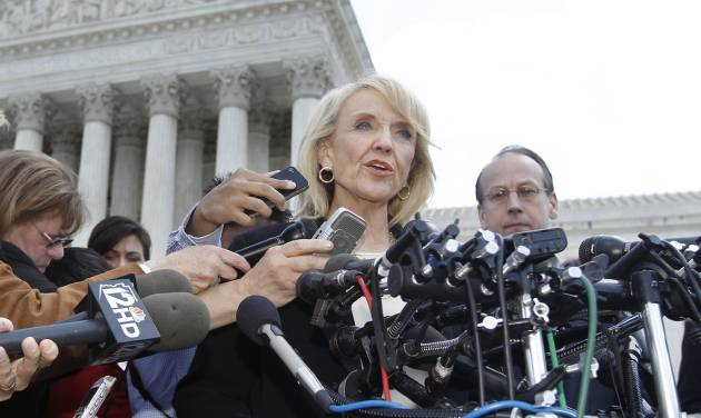 """FILE - In this Wednesday, April 25, 2012 file photo, Arizona Gov. Jan Brewer speaks to reporters after the Supreme Court questioned Arizona's """"show me your papers"""" immigration law in front of the Supreme Court in Washington. On Thursday, Sept. 6, 2012, Brewer's office said the most contentious section of Arizona's immigration law is expected to go into effect shortly. A spokesman says Brewer is pleased with a federal judge's decision on Wednesday, Sept. 5, 2012 to allow enforcement of the law. It enables officers, while enforcing other laws, to question the immigration status of those they suspect are in the country illegally. The National Immigration Law Center says it's considering """"legal options"""" after the ruling. (AP Photo/Charles Dharapak)"""