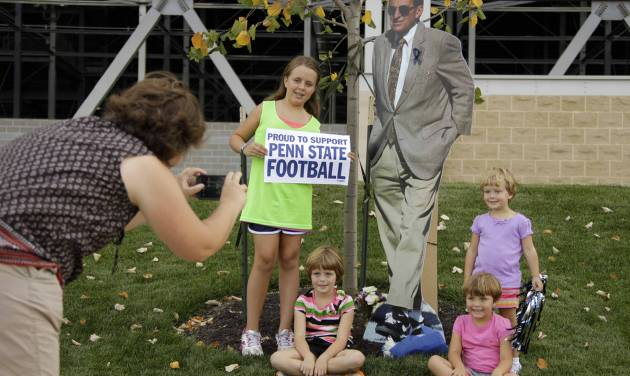 FILE - This Aug. 31, 2012 file photo shows Sarah Brown, left, of Kutztown, Pa., taking a picture of her children, from left, Molly, Caroline, Susanna, and Eloise next to a cardboard cutout of former Penn State head football coach Joe Paterno, outside Beaver Stadium on Penn State's main campus in State College, Pa. The bronzed statue outside Beaver Stadium is gone. The record of 409 career victories erased by the NCAA. But reminders of the late coach Paterno still abound on Penn State football game days. (AP Photo/Gene J. Puskar, File)