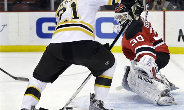 Boston Bruins' Loui Eriksson, of Sweden, (21) shoots for a goal past New Jersey Devils goalie Martin Brodeur (30) during the first period of an NHL hockey game in Newark, N.J., Sunday, April 13, 2014. (AP Photo/Mel Evans)