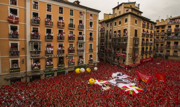 "Revelers hold up traditional red neckties during the launch of the ""Chupinazo"" rocket, to celebrate the official opening of the 2014 San Fermin fiestas in Pamplona, Spain, Sunday, July 6, 2014. Revelers from around the world turned out here to kick off the festival with a messy party in the Pamplona town square, one day before the first of eight days of the running of the bulls glorified by Ernest Hemingway's 1926 novel ""The Sun Also Rises."" (AP Photo/Andres Kudacki)"