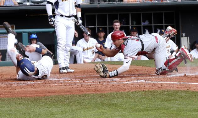 Oklahoma\'s Renae Martinez tags Ray Guerinni out at home as the West Virginia Mountaineers...
