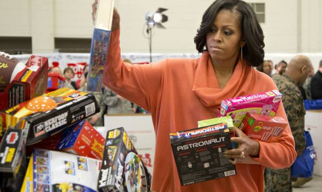 First lady Michelle Obama, puts some presents in a container as she helps sort out toys and gifts during her visit at the Joint Base Anacostia-Bolling to deliver toys and gifts to the Marine Corps' Toys for Tots campaign in Washington, Tuesday, Dec. 11, 2012.  (AP Photo/Manuel Balce Ceneta)