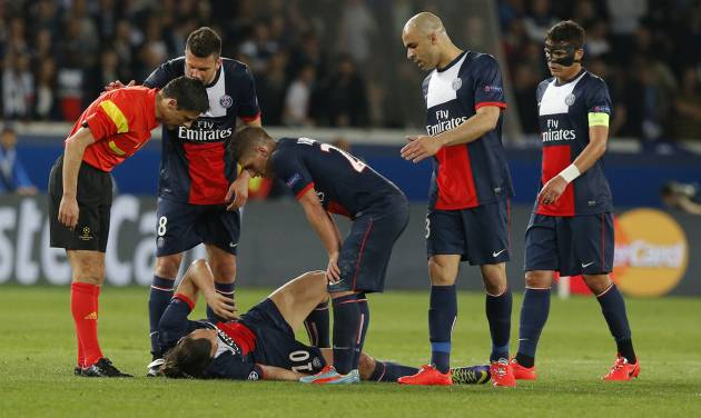 Paris Saint-Germain's Zlatan Ibrahimovic lies on the ground injured as his teammates and the referee look on during a Champions League quarterfinal first leg soccer match between Paris Saint-Germain and Chelsea at Parc des Princes stadium in Paris, Wednesday, April 2, 2014. (AP Photo/Michel Euler)