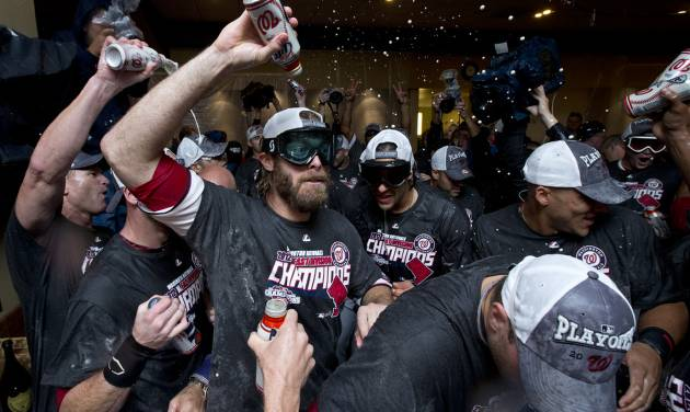 Washington Nationals right fielder Jayson Werth, center, celebrates with teammates after clutching the National League East division title following a baseball game against the Philadelphia Phillies in Washington, Monday, Oct. 1, 2012. (AP Photo/Manuel Balce Ceneta)