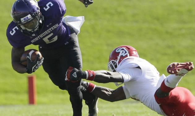 Northwestern running back Venric Mark (5) is tackled by South Dakota defensive back Chris Frierson (7) during the first half of an NCAA college football game in Evanston, Ill., Saturday, Sept. 22, 2012. Northwestern won 38-7. (AP Photo/Nam Y. Huh)