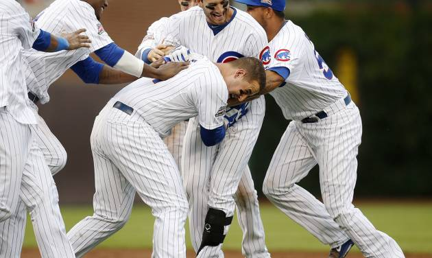 Chicago Cubs players pile onto Justin Ruggiano, center, after Ruggiano hit a game winning RBI single against the Atlanta Braves during the ninth inning of a baseball game on Friday, July 11, 2014, in Chicago. The Chicago Cubs won 5-4. (AP Photo/Andrew A. Nelles)