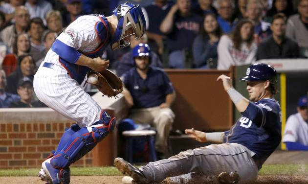 Chicago Cubs catcher John Baker, left, is unable to handle a throw from third baseman Luis Valbuena and get the force on San Diego Padres' Yasmani Grandal during the sixth inning of a baseball game Thursday, July 24, 2014, in Chicago. Valbuena was charged with an error on the play. (AP Photo/Charles Rex Arbogast)