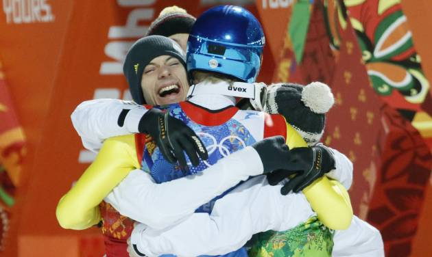 Germany's Andreas Wank, left, hugs huis teammates after winning the gold during the ski jumping large hill team competition at the 2014 Winter Olympics, Monday, Feb. 17, 2014, in Krasnaya Polyana, Russia. (AP Photo/Dmitry Lovetsky)