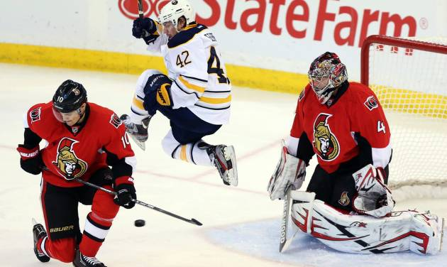 Buffalo Sabres' Nathan Gerbe (42) jumps as he screens a shot on Ottawa Senators goaltender Craig Anderson (41) as Mike Lundin (10) watches during the first period of their NHL hockey game, Tuesday, Feb. 12, 2013, in Ottawa, Ontario. (AP Photo/The Canadian Press, Fred Chartrand)