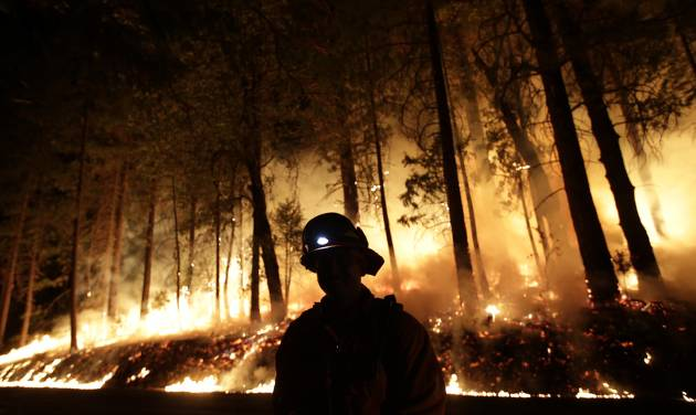 A firefighter watches for spot fires during a burnout operation while battling the Rim Fire near Yosemite National Park, Calif., on Sunday, Aug. 25, 2013. Fire crews are clearing brush and setting sprinklers to protect two groves of giant sequoias as a massive week-old wildfire rages along the remote northwest edge of Yosemite National Park. (AP Photo/Jae C. Hong)