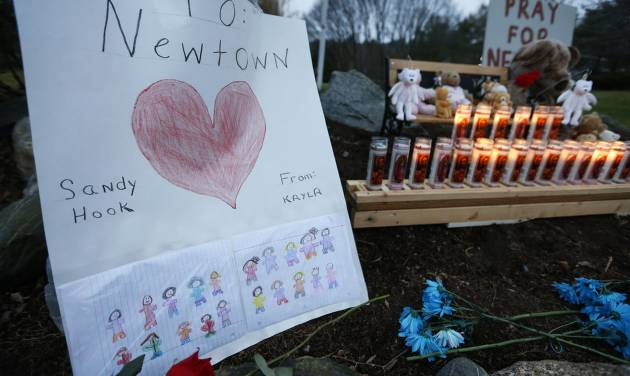 A child's message rests with a memorial for shooting victims, Sunday, Dec. 16, 2012, in Newtown, Conn. A gunman walked into Sandy Hook Elementary School in Newtown on Friday and opened fire, killing 26 people, including 20 children. (AP Photo/Jason DeCrow)