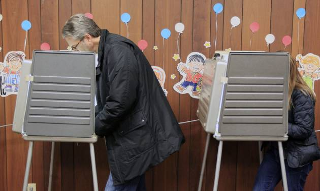 A man and woman vote at Hyde Park Public Library, Tuesday, Nov. 6, 2012, in Cincinnati. After a grinding presidential campaign, Americans head into polling places across the country.(AP Photo/Al Behrman)