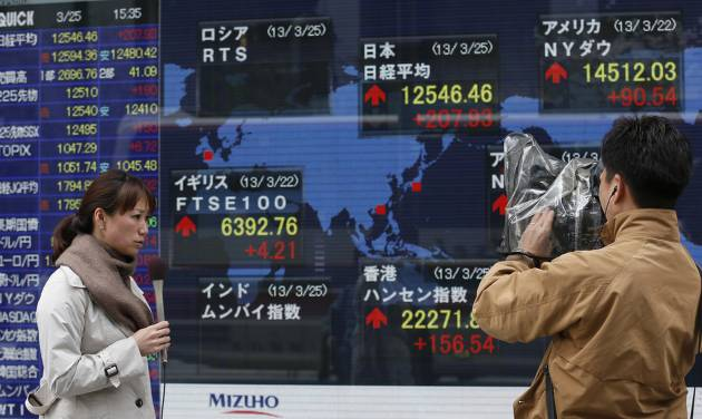 A TV crew reports stock princes in front of an electronic stock indicator of a securities firm in Tokyo, Monday, March 25, 2013. A last-minute package of rescue loans that saves Cyprus from a banking collapse and bankruptcy helped push Asian stock markets higher Monday. Japan's Nikkei 225 index surged 1.9 percent to 12,546.46. (AP Photo/Shizuo Kambayashi)