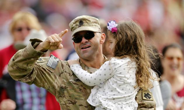 A military servicemman surprises his family on the field during the college football game between the University of Oklahoma Sooners (OU) and the Iowa State University Cyclones (ISU) at Gaylord Family-Oklahoma Memorial Stadium in Norman, Okla. on Saturday, Nov. 16, 2013. Photo by Steve Sisney, The Oklahoman