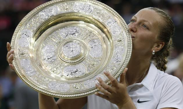 Petra Kvitova of Czech Republic kisses the trophy after winning the women's singles final against Eugenie Bouchard of Canada at the All England Lawn Tennis Championships in Wimbledon, London, Saturday July 5, 2014. (AP Photo/Sang Tan)