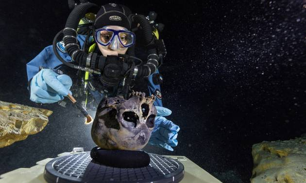 In this June 2013 photo provided by National Geographic, diver Susan Bird, working at the bottom of Hoyo Negro, a large dome-shaped underwater cave in Mexico's Yucatan Peninsula, brushes a human skull found at the site while her team members take detailed photographs. Thousands of years ago, a teenage girl fell into this deep hole and died. Now, her skeleton and her DNA are helping scientists study the origins of the first Americans. An analysis of her remains was released Thursday, May 15, 2014 by the journal Science. Her DNA links her to an ancient land bridge connecting Asia and North America, and suggests she shares ancestors with the modern native peoples of the Americas. (AP Photo/National Geographic, Paul Nicklen)