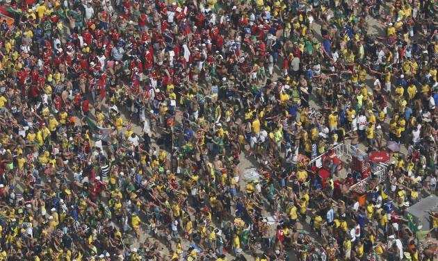 Soccer fans gather before a live broadcast of the World Cup round of 16 match between Brazil and Chile, inside the FIFA Fan Fest area on Copacabana beach, in Rio de Janeiro, Brazil, Saturday, June 28, 2014. (AP Photo/Silvia Izquierdo)
