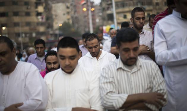 Egyptian men pray on a street next to the Sayyida Zeinab mosque on the first day of Eid al-Ahda in Cairo, Egypt, Tuesday, Oct. 15, 2013. Muslims worldwide are celebrating Eid al-Adha, or the Feast of the Sacrifice, by sacrificial killing of sheep, goats, cows or camels. The slaughter commemorates the biblical story of Abraham, who was on the verge of sacrificing his son to obey God's command, when God interceded by substituting a ram in the child's place. (AP Photo/Manu Brabo)