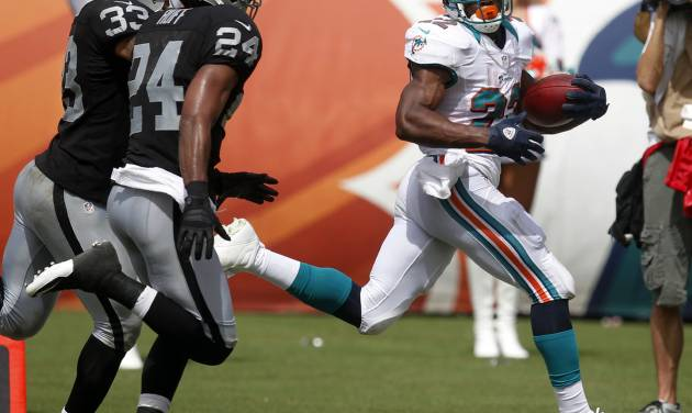 Miami Dolphins running back Reggie Bush (22) looks back toward Oakland Raiders free safety Michael Huff (24) and strong safety Tyvon Branch (33) while approaching the end zone during the second half of an NFL football game on Sunday, Sept. 16, 2012, in Miami. (AP Photo/Wilfredo Lee)