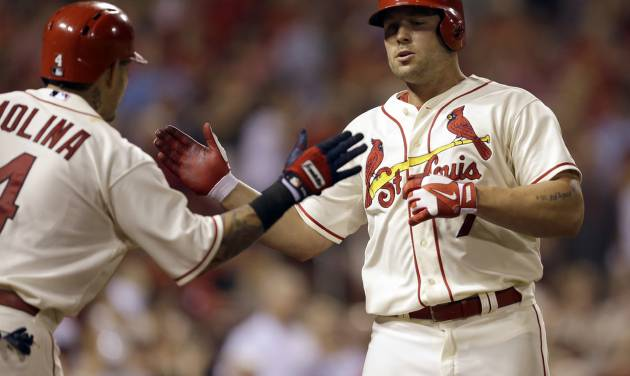 St. Louis Cardinals' Matt Holliday, right, is congratulated by teammate Yadier Molina after hitting a solo home run during the eighth inning in the second baseball game of a doubleheader against the Chicago Cubs Saturday, Aug. 30, 2014, in St. Louis. The home run was Holliday's second of the game. (AP Photo/Jeff Roberson)