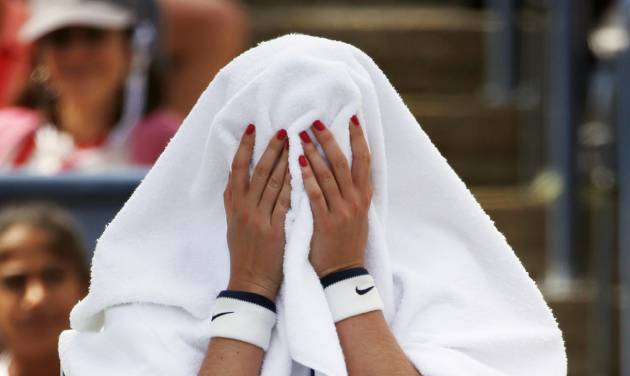 Petra Kvitova, of the Czech Republic, covers her head with a towel during a break between games against Aleksandra Krunic, of Serbia, during the third round of the 2014 U.S. Open tennis tournament, Saturday, Aug. 30, 2014, in New York. (AP Photo/Kathy Willens)