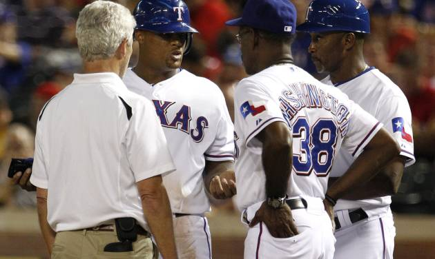 Texas Rangers athletic trainer Jamie Reed, left, manager Ron Washington (38) and first base coach Gary Pettis, talk with Adrian Beltre, center rear, after being walked in the third inning of a baseball game against the Cleveland Indians, Wednesday, Sept. 12, 2012, in Arlington, Texas. Beltre left the game following the inning with a shoulder injury. (AP Photo/Tony Gutierrez)