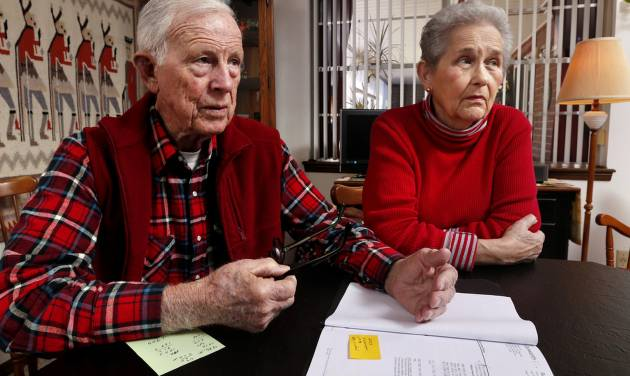 Robert and Sharron Ashton review information about their Genworth long-term care insurance policies at their home in Norman. [PHOTO BY STEVE SISNEY]