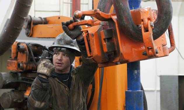 FILE - In this Dec. 5, 2013 file photo, Russell Girsh motions to his driller to turn the equipment on at an oil rig near Watford City, N.D. The AFL-CIO, the nation's largest labor federation, says the death rate for oil, gas and mining workers in North Dakota was more than six times the national average in 2012. It says the state had a fatality rate of 104 per 100,000 workers in those industries. North Dakota had the highest worker death rate in the nation in 2012 with 17.7 deaths per 100,000 workers. (AP Photo/Williston Herald, Jerry Burnes, File)