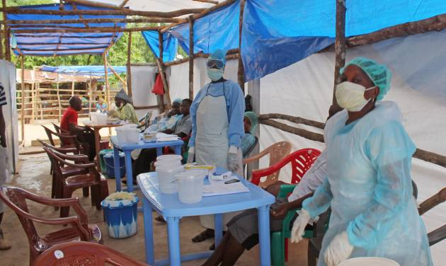 In this photo taken on Sunday, July 27, 2014,  Medical personnel inside a clinic taking care of Ebola patients in the Kenema District on the outskirts of Kenema, Sierra Leone.  Liberia President Ellen Johnson Sirleaf has closed some border crossings and ordered strict quarantines of communities affected by the Ebola outbreak. The announcement late Sunday came a day after Sirleaf formed a new taskforce charged with containing the disease, which has killed 129 people in the country and more than 670 across the region.(AP Photo/ Youssouf Bah)